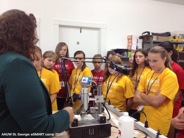 AAUW St. G eSMART 2014 Girls checking out equipment that removes the chip from cell phones for when evidence is hidden behind a password.